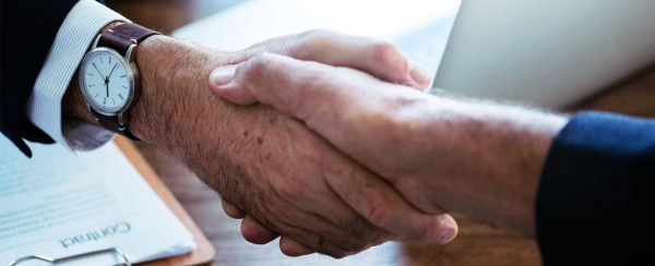 image of customer and sales rep shaking hands illustrating retention